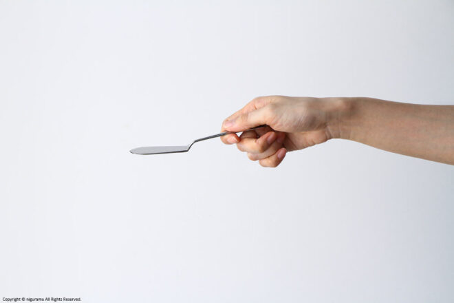 """Compare the size of the """"Deco, Butter Knife"""" and the hand."""